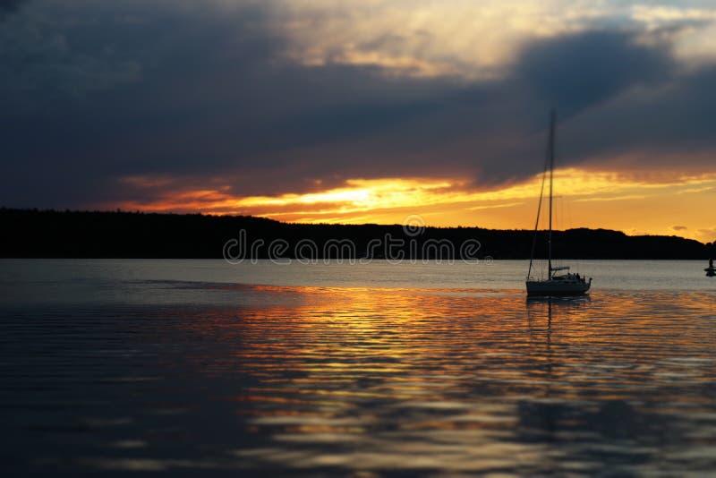 Folgen Sie dem Sonnenuntergang im ruhigen See mit dem Segelboot lizenzfreie stockfotografie