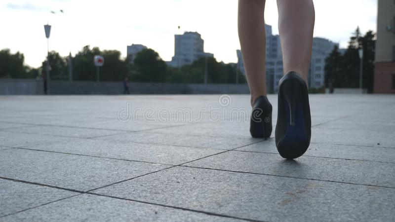 Folgen Sie zu den weiblichen Beinen in den Schuhen der hohen Absätze, die in die städtische Straße gehen Füße der jungen Geschäft stockfoto