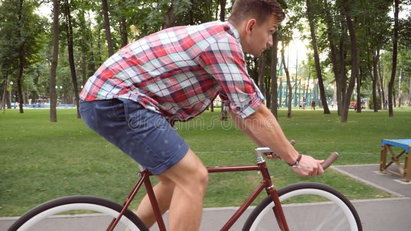 Folgen Sie zum jungen gutaussehenden Mann, der Weinlesefahrrad im Freienfährt Sportlicher Kerl, der am Park radfährt Gesunder akt lizenzfreie stockfotos