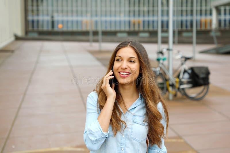Folgender Frauengenerationsunternehmer Junge erfolgreiche Geschäftsfrau, die auf Mobiltelefon außerhalb ihres Bürogebäudes sprich stockbilder