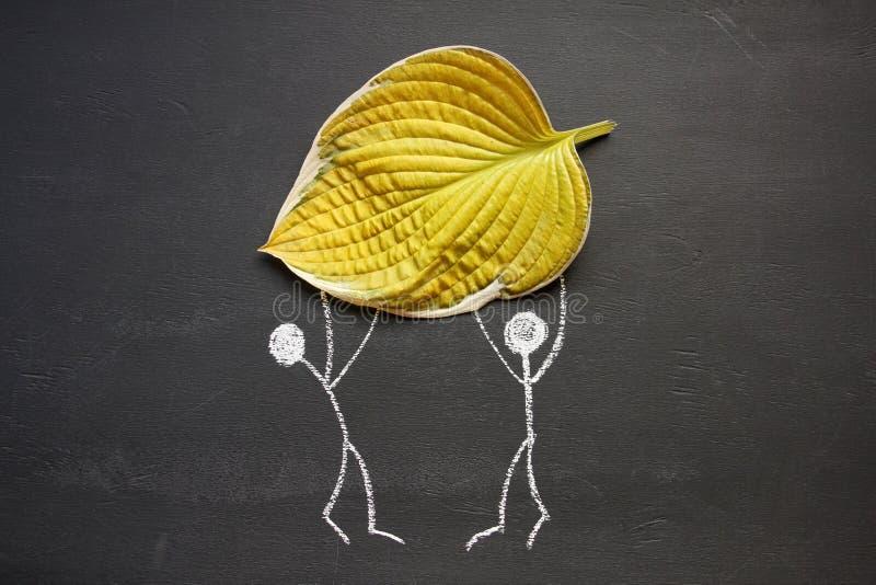 Folha amarela do outono grande do holdind de dois povos do desenho de giz nas mãos Fundo do quadro-negro ou do quadro Queda ou co fotos de stock