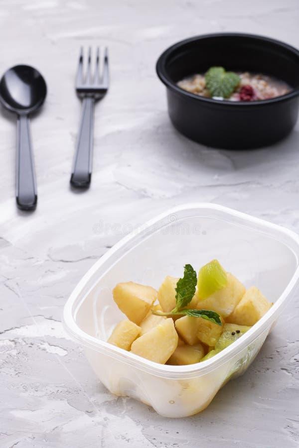 Folha da hortelã com frutos exóticos no recipiente de alimento plástico, fundo borrado foto de stock