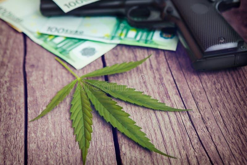 Folha da marijuana com contas da arma e de dinheiro fotos de stock royalty free