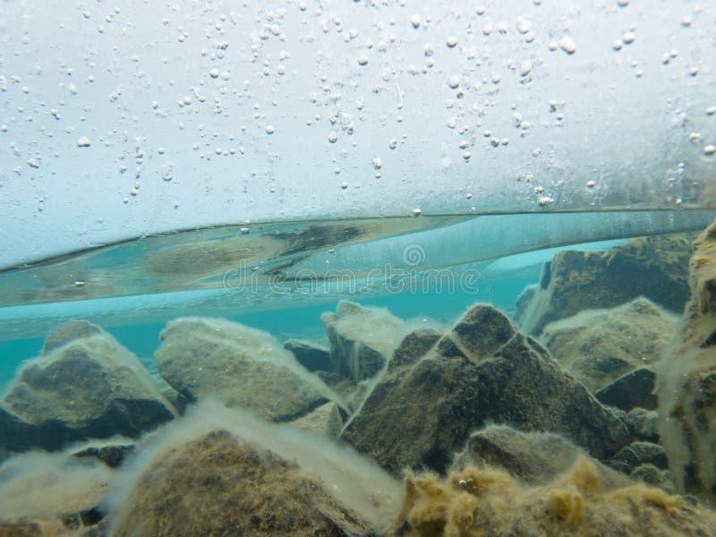 Folha de gelo grossa subaquática sobre a parte inferior de lago rochosa fotos de stock royalty free