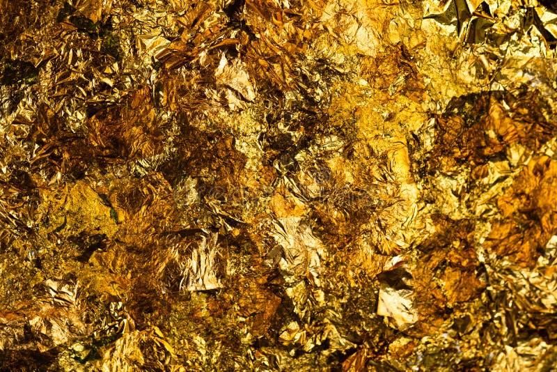 Folha de ouro amarelo ou sucatas brilhantes da textura do fundo da folha de ouro fotografia de stock