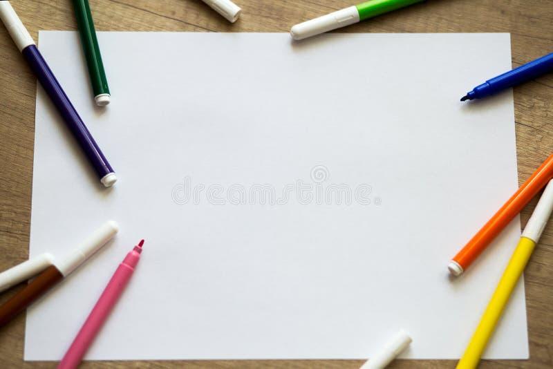 Folha de papel branca, canetas com ponta de feltro coloridas em um fundo de madeira imagens de stock