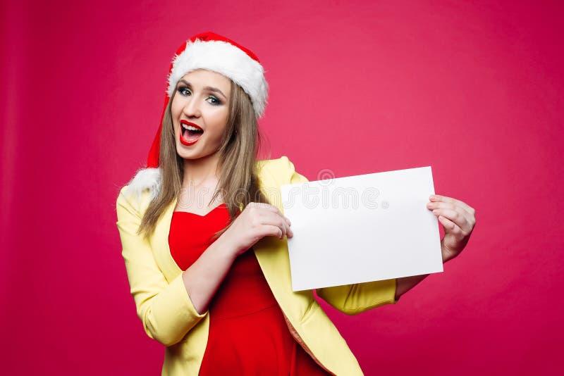 Folha de papel da placa da menina de sorriso no chapéu de Santa fotografia de stock royalty free