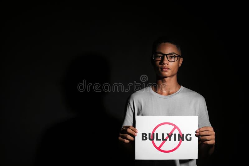 Folha de papel da terra arrendada do adolescente afro-americano com palavra PARADA no fundo escuro imagem de stock royalty free