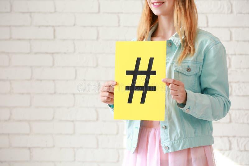 Folha de papel da terra arrendada da mulher com sinal do hashtag no fundo branco do tijolo foto de stock royalty free