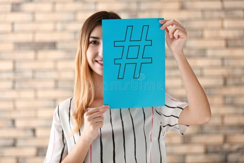 Folha de papel da terra arrendada da mulher com sinal do hashtag no fundo do tijolo fotos de stock royalty free