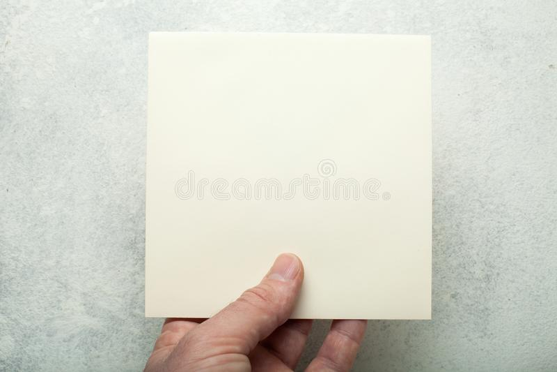 Folha de papel quadrada bege em uma mão europeia, close-up Modelo fotografia de stock