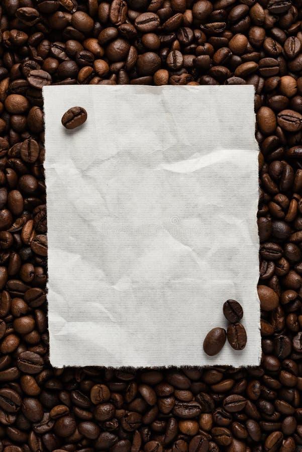 Folha de papel vazia branca no fundo de feijões de café roasted para o menu ou a receita do texto imagem de stock royalty free
