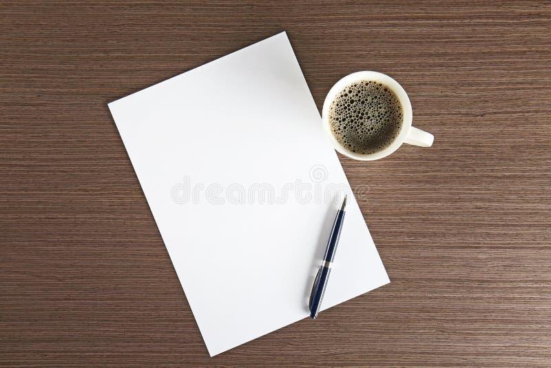 Folha de papel vazia com pena e xícara de café na tabela foto de stock