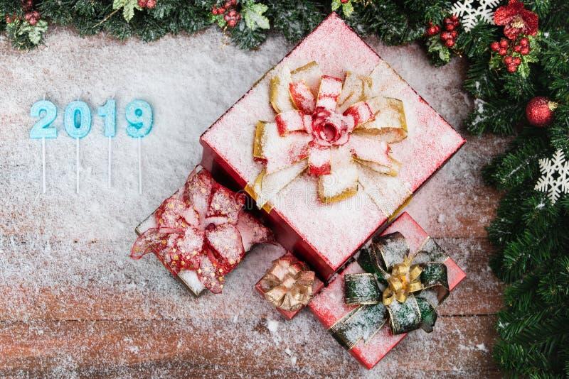 A folha de prova azul da cor do ano 2019 na placa de madeira, caixas de presente vermelhas no lado tem a neve por todo o lado em foto de stock royalty free