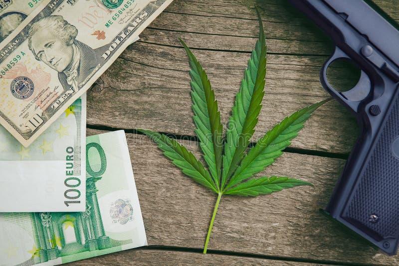 Folha do cannabis Arma e dinheiro em torno da folha fotografia de stock