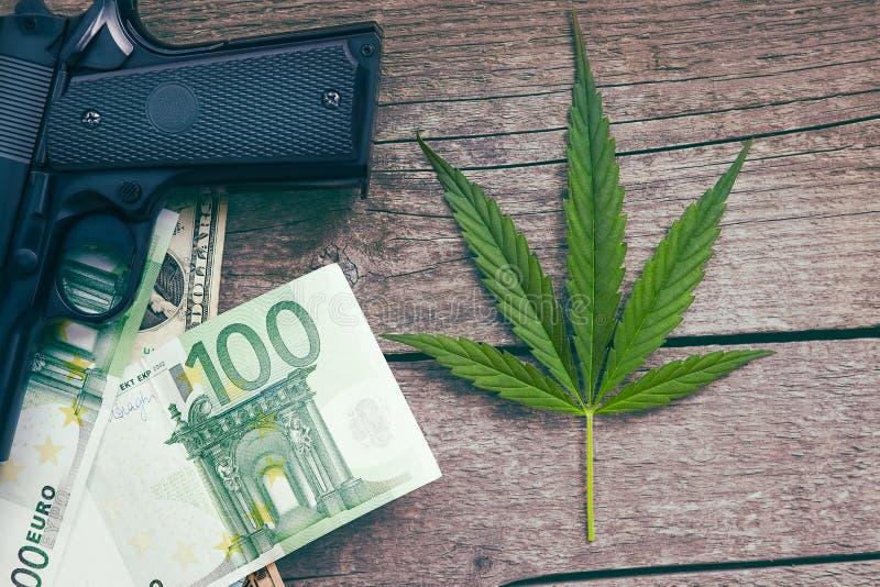 Folha do cannabis com a euro- contas e arma imagens de stock royalty free