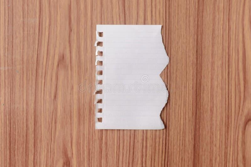 A folha do papel do caderno com placa rasgada da borda rasgou a parte no isolado sobre o fundo de madeira da tabela Forma danific imagens de stock