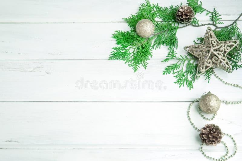 Folha do pinho com a decoração de prata da bola da estrela e do Natal na placa de madeira branca com espaço da cópia, ano novo fe foto de stock