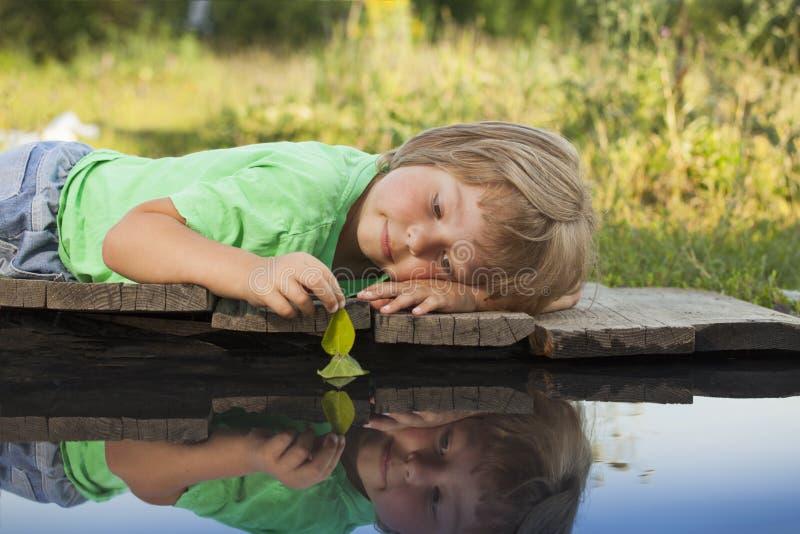 Folha-navio verde na mão das crianças na água, menino no jogo do parque com o barco no rio fotografia de stock