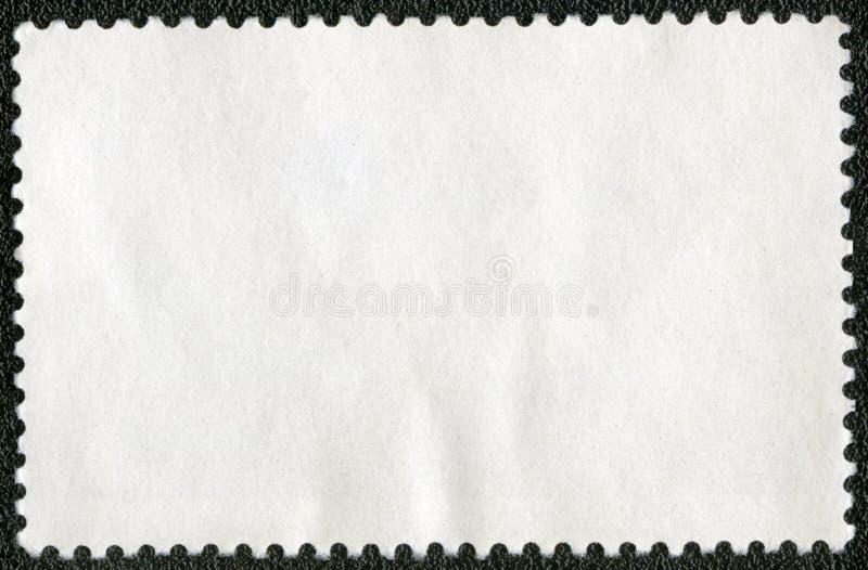 Folha vazia do selo postal em um fundo preto fotografia de stock royalty free