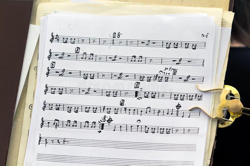 Folhas com as notas musicais escritas à mão em um suporte, fundo foto de stock