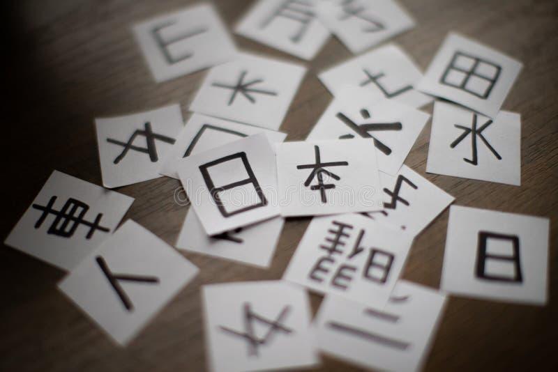 Folhas com muito kanji dos caráteres da língua chinesa e japonesa com palavra principal Japão imagem de stock