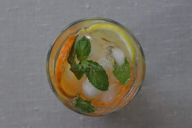 Folhas da laranja, do limão e de hortelã no fundo bege foto de stock