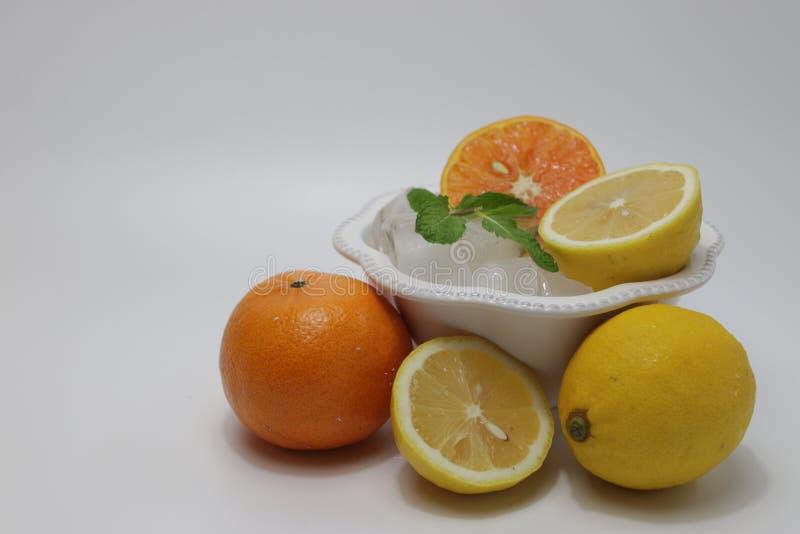 Folhas da laranja, do limão e de hortelã no fundo bege imagem de stock royalty free