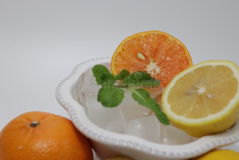 Folhas da laranja, do limão e de hortelã no fundo bege fotografia de stock royalty free