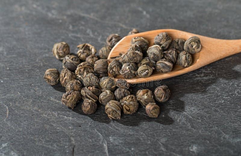 Folhas de chá secas em colheres de madeira fotografia de stock royalty free