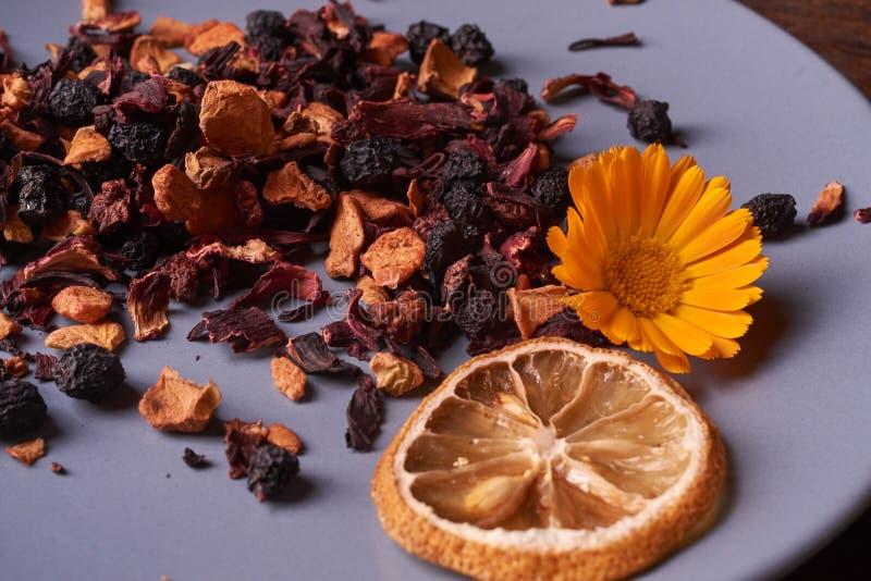 Folhas de chá secas pretas do fruto na placa azul na tabela de madeira Foco seletivo imagem de stock