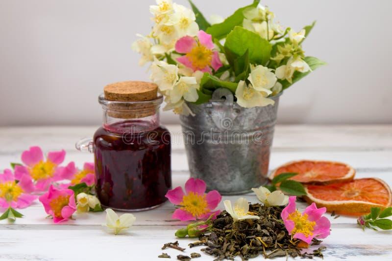 Folhas de chá verdes secas do jasmim com flores do jasmim, com as flores de rosas e do doce de framboesa selvagens fotos de stock royalty free