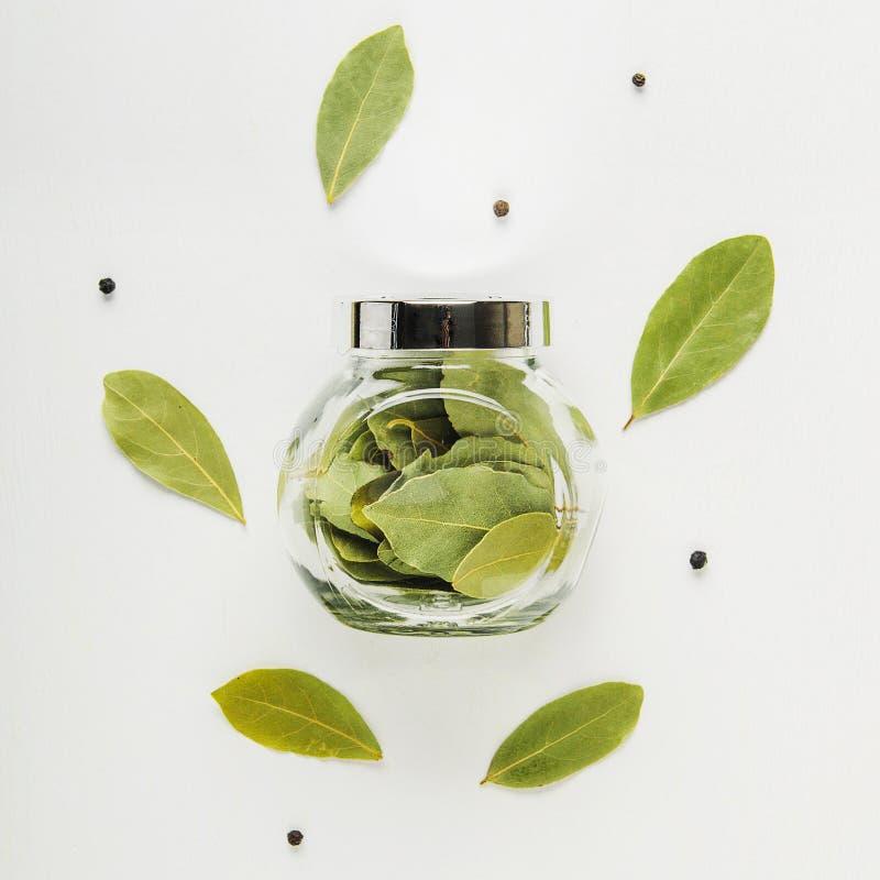Folhas de louro e pimenta preta secadas no fundo branco Frasco de vidro para especiarias Tempero útil Vista superior imagem de stock