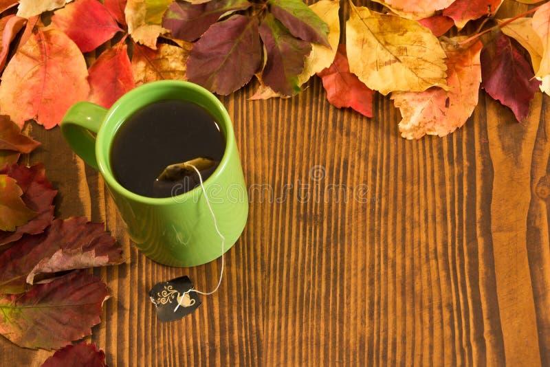 Folhas de outono e copo de chá sobre o fundo de madeira fotografia de stock