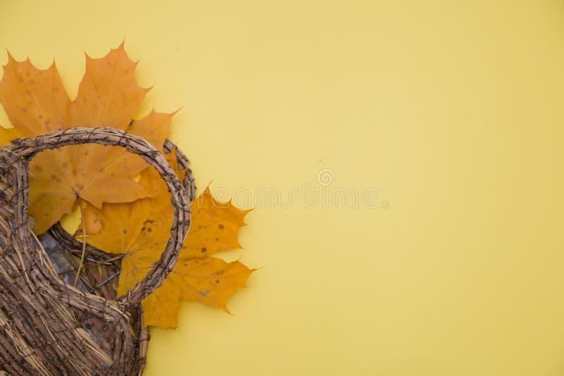 Folhas de outono e uma cesta em um fundo amarelo, o conceito do outono imagens de stock