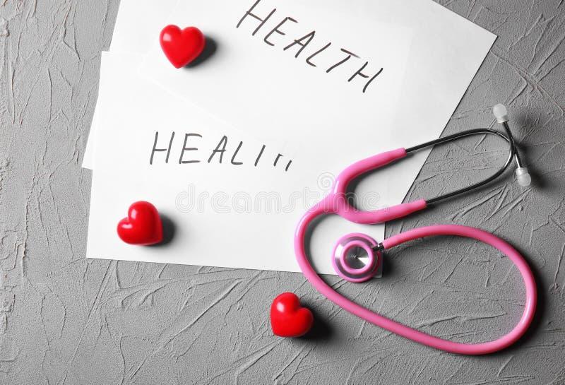 Folhas de papel com palavra SAÚDE e estetoscópio médico no fundo cinzento imagem de stock royalty free