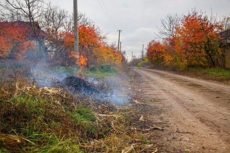 Folhas de queimadura, fogo ao limpar o jardim Tarefas do outono na exploração agrícola fotos de stock royalty free