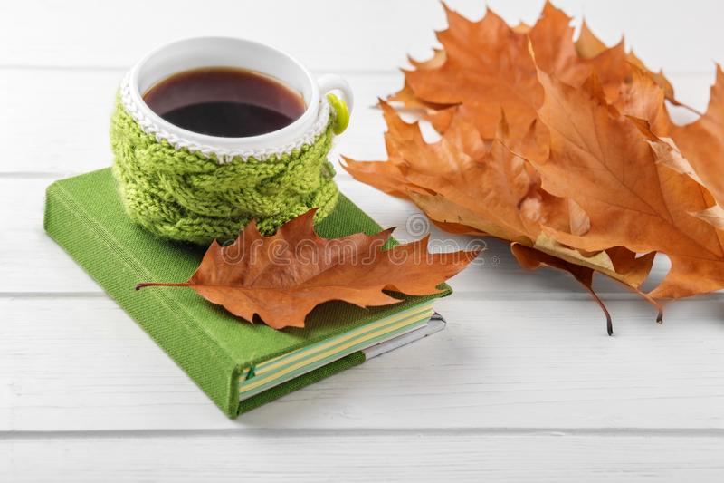 Folhas de uma xícara de café e do amarelo e um caderno O conceito do outono, ainda vida, abrandamento, estudo imagem de stock