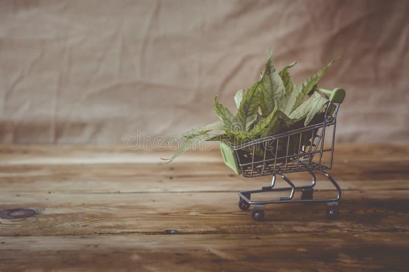 Folhas do cannabis no carrinho de compras Compra da droga, legalização da marijuana, conceito do negócio da droga fotografia de stock royalty free