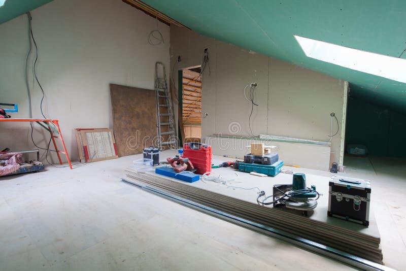 Folhas do drywall, peças do andaime, ferramentas do punho e material de construção na sala do apartamento durante na remodelação fotografia de stock