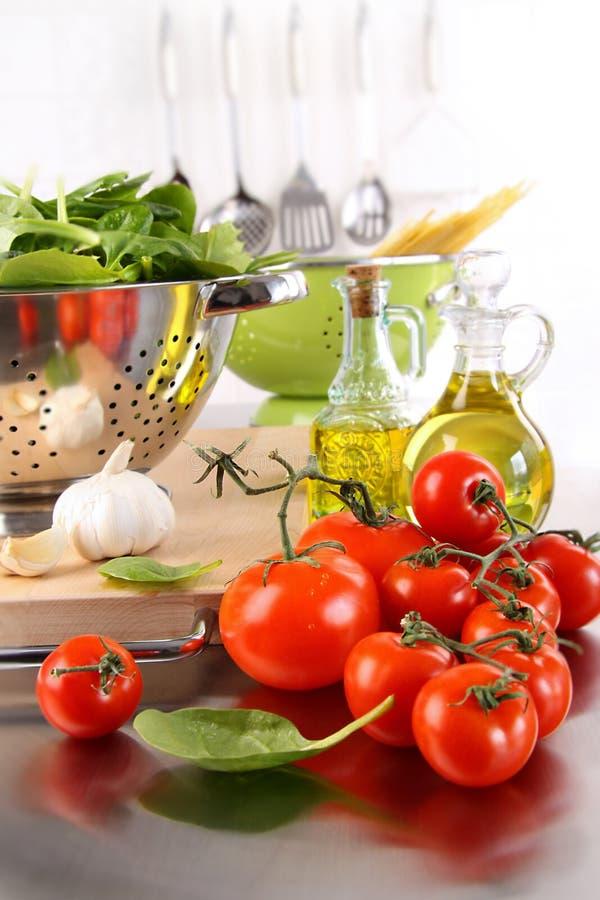 Folhas do espinafre no filtro com tomates fotos de stock