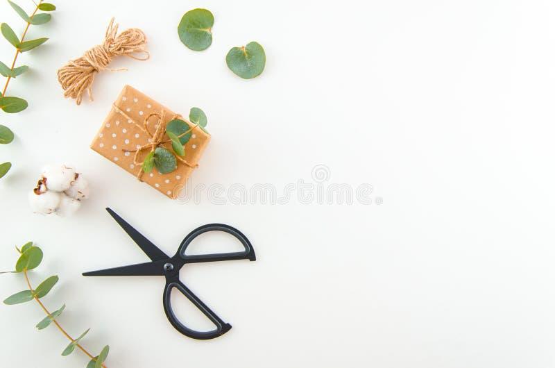 Folhas do eucalipto e flores e caixas de presente do algodão que embalam no fundo branco com tesouras Configura??o lisa, vista su fotografia de stock