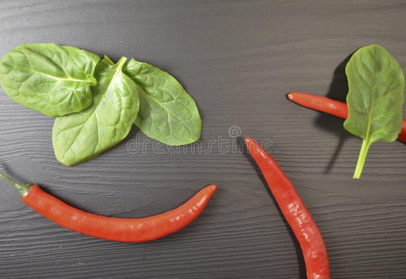 Folhas dos espinafres e pimentas de pimentão vermelho no fundo preto fotos de stock royalty free
