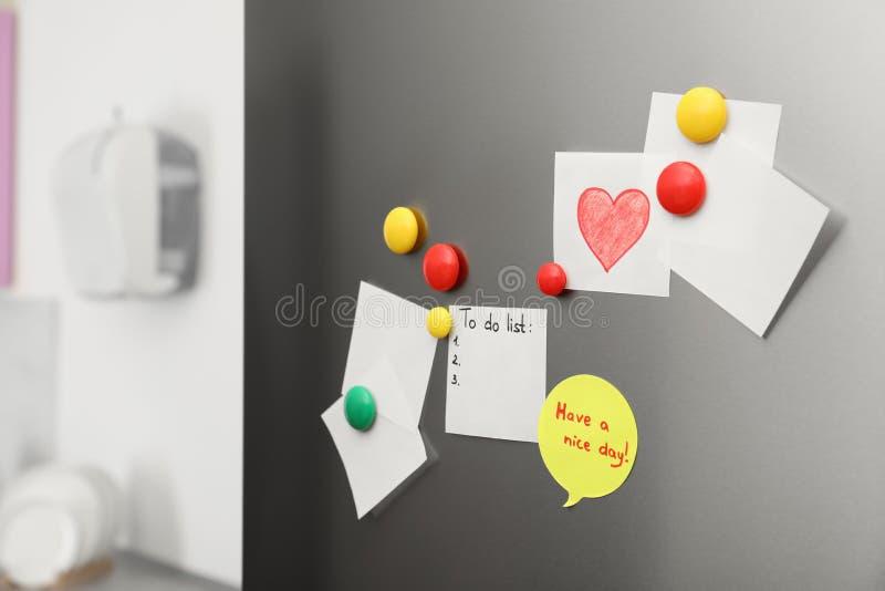 Folhas e ímãs de papel na porta do refrigerador imagens de stock royalty free
