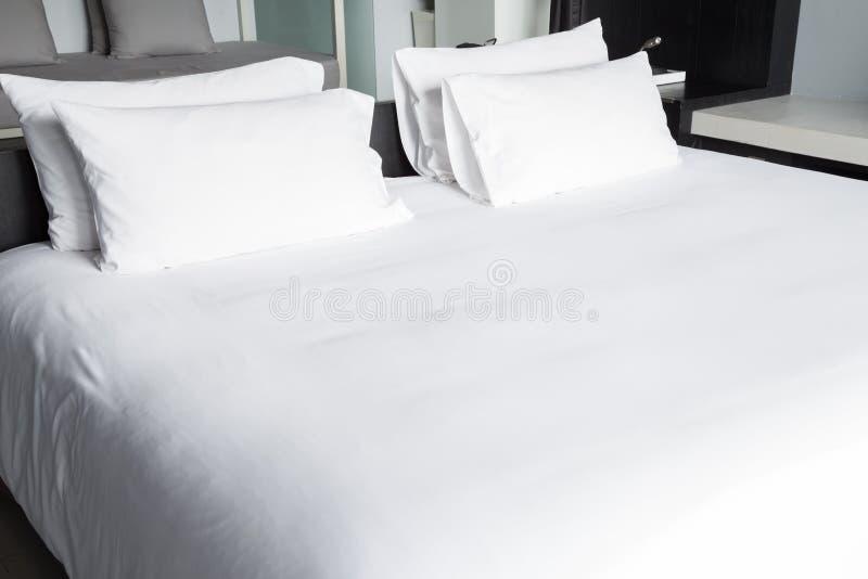 Folhas e descansos brancos de cama fotografia de stock royalty free