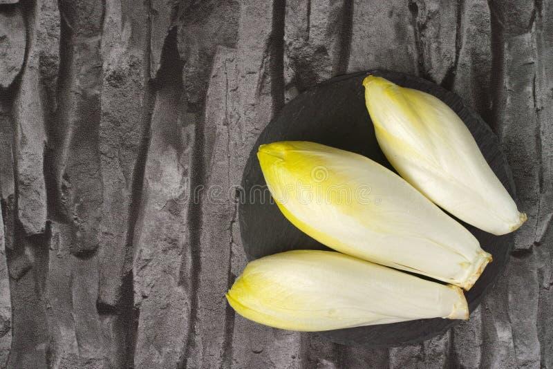 Folhas frescas da salada da chicória colocadas em uma placa de pedra cinzenta imagem de stock royalty free