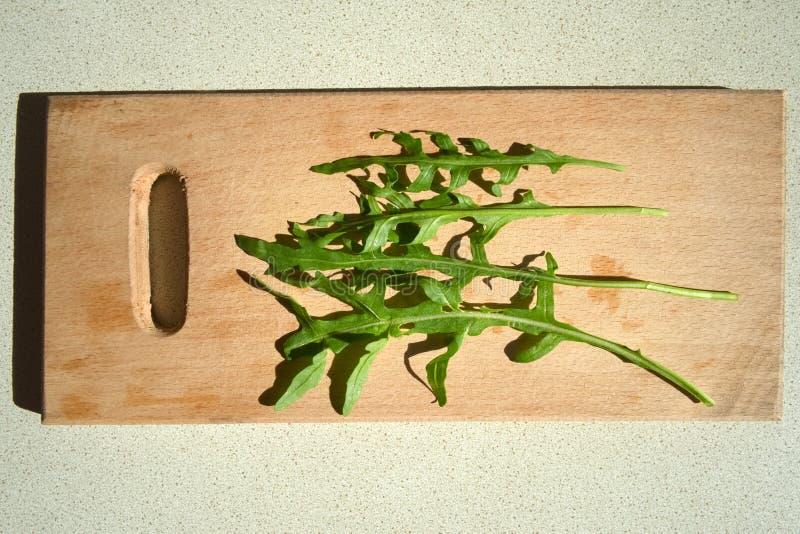 Folhas frescas verdes da rúcula em uma placa de corte fotografia de stock