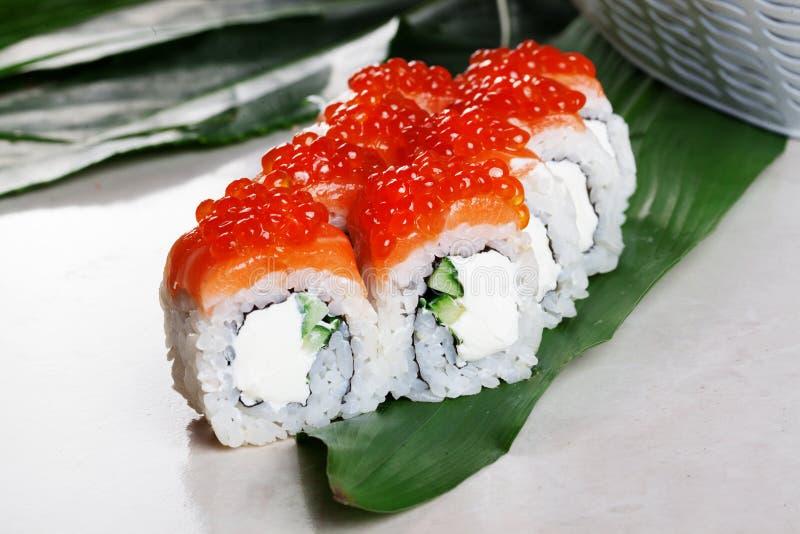 Folhas tropicais do caviar vermelho do sushi do rolo de Philadelphfia fotografia de stock royalty free