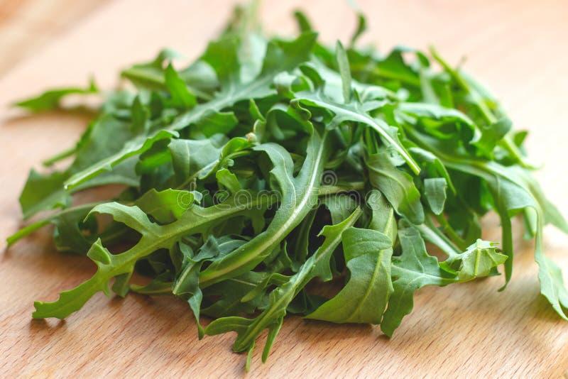 Folhas verdes saudáveis frescas da rúcula no fundo de madeira claro imagens de stock royalty free