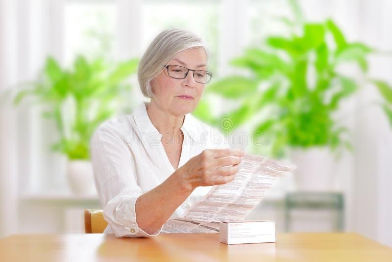 Folheto do pacote da droga da leitura da mulher fotografia de stock